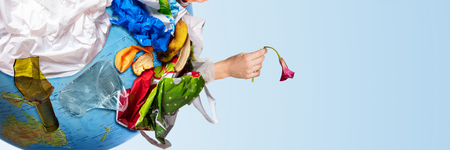 An earth globe covered with trash and male hand with a withering flower over white background, the concept of ecology problem and World Environment Day. Photo with message for social advertising, place for inscription Standard-Bild - 117754517