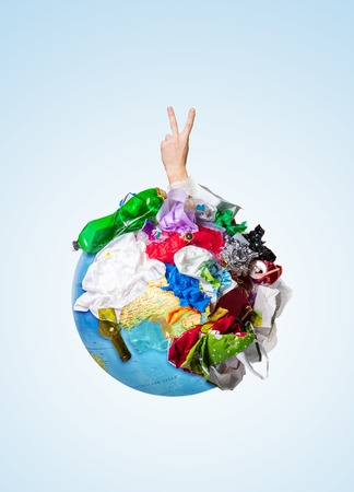An earth globe covered with trash and male hand with a gesture of victory over white background, the concept of ecology problem and World Environment Day. Photo with message for social advertising Banco de Imagens