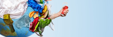 An earth globe covered with trash and male hand squeezing aluminum can over white background, the concept of ecology problem and World Environment Day. Photo with message for social advertising, place for inscription