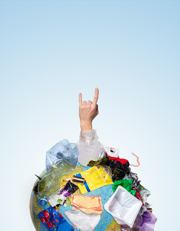 An earth globe covered with trash and male hand with a horns over white background, the concept of ecology problem and World Environment Day. Photo with message for social advertising, place for inscription