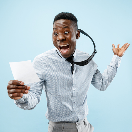 Young afro man with a surprised happy expression won a bet on blue studio background. Human facial emotions and betting concept. Trendy colors