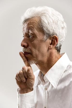 Serious senior frightened male keeps fore finger on lips, tries to keep conspiracy, says: Shh, make silence please. Isolated shot of man shows silence gesture