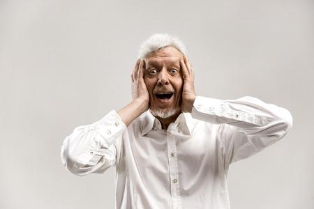 Wauw. Senior mannelijke halve lengte portret op grijze studio achtergrondgeluid. Volwassen emotioneel verrast bebaarde man met open mond. Menselijke emoties, gezichtsuitdrukking concept. Trendy kleuren