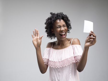 Young african woman with a surprised happy expression won a bet on gray studio background. Human facial emotions and betting concept. Trendy colors