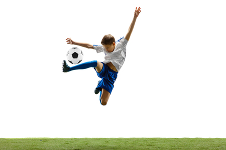Young boy with soccer ball running and jumping isolated on white. football soccer player in motion on studio background. Standard-Bild