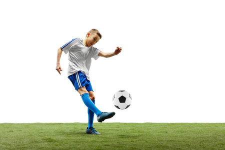 Young boy with soccer ball running and jumping isolated on white. football soccer player in motion on studio background. Archivio Fotografico