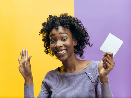 Young african woman with a surprised happy expression won a bet on studio background. Human facial emotions and betting concept. Trendy colors Stock Photo