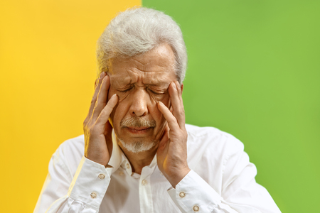 Portrait of upset old man covering face while crying. Isolated on color background