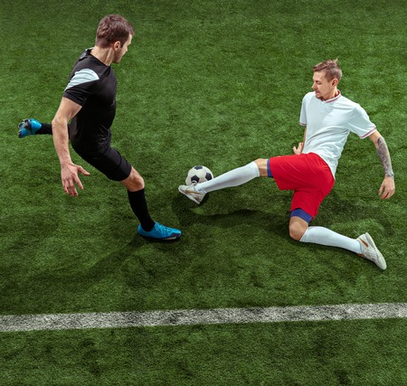 Football player tackling for ball over green grass background. Professional male soccer players in motion at stadium. Fit jumping men in action, jump, movement at game. Фото со стока