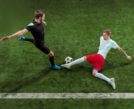 Football player tackling for ball over green grass background. Professional male soccer players in motion at stadium. Fit jumping men in action, jump, movement at game. 版權商用圖片