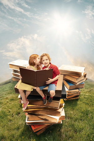 Little girl and boy sitting on the tower made of big books. Childhood dreams, creative and education concept. Wondering world. abstract collage
