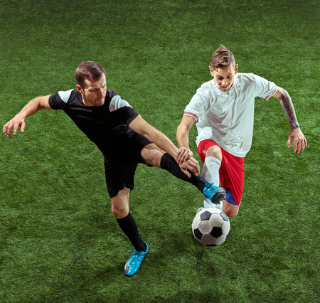 Football player tackling for ball over green grass background. Professional male soccer players in motion at stadium. Fit jumping men in action, jump, movement at game. Banco de Imagens