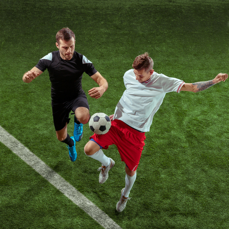 Football player tackling for ball over green grass background. Professional male soccer players in motion at stadium. Fit jumping men in action, jump, movement at game. 스톡 콘텐츠