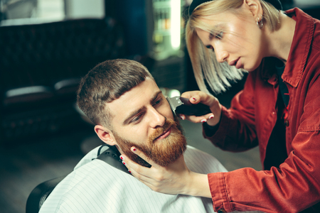 Client during beard shaving in barbershop. Female barber at salon. Gender equality. Woman in the male profession. Stock fotó - 118033197