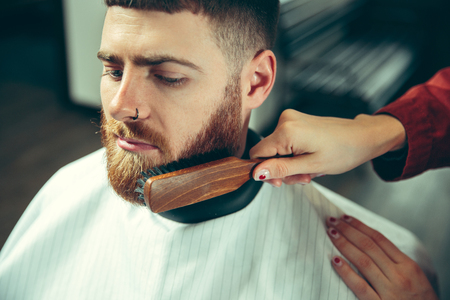 Client during beard shaving in barbershop. Female barber at salon. Gender equality. Woman in the male profession. Hands close up Stock Photo