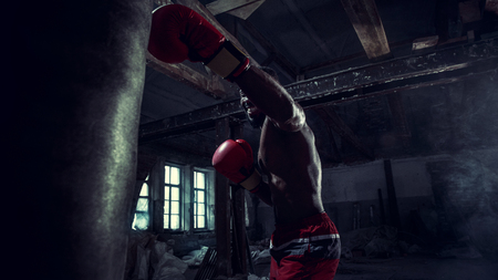 Hands of boxer over dark gym background. Strength, attack and motion concept. Fit african american model in movement. Naked muscular athlete in red gloves. Sporty man during boxing Stockfoto - 118033099