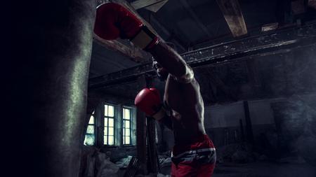 Mani del pugile su sfondo scuro palestra. Forza, attacco e concetto di movimento. Fit modello afroamericano in movimento. Atleta muscolare nudo in guanti rossi. Uomo sportivo durante la boxe