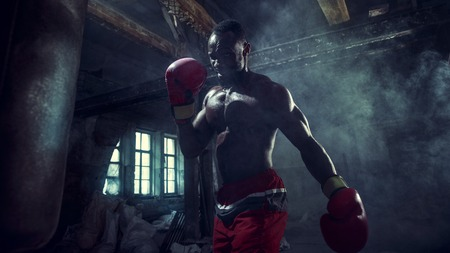 Hands of boxer over dark gym background. Strength, attack and motion concept. Fit african american model in movement. Naked muscular athlete in red gloves. Sporty man during boxing