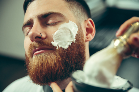 Client during beard shaving in barbershop. Female barber at salon. Gender equality. Woman in the male profession. Hands close up Zdjęcie Seryjne