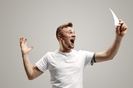 Young caucasian man with a surprised happy expression won a bet on gray studio background. Human facial emotions and betting concept Stockfoto