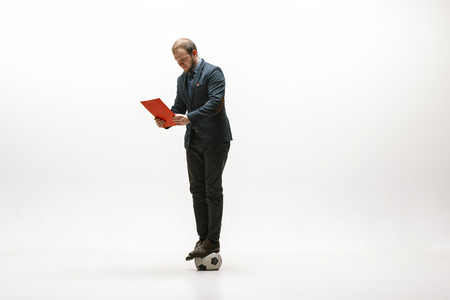 Businessman with clipboard and football ball in office. Soccer freestyle. Concept of balance and agility in business. Manager perfoming tricks isolated on white studio background.