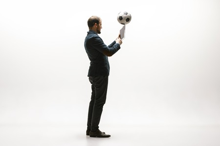 Businessman with tablet and football ball in office. Soccer freestyle. Concept of balance and agility in business. Manager perfoming tricks isolated on white studio background. Stock Photo