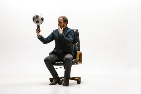 Businessman with football ball in office. Soccer freestyle. Concept of balance and agility in business. Manager perfoming tricks sitting on chair and making a bet with a smartphone isolated on white studio background.
