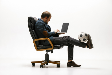 Businessman with football ball in office. Soccer freestyle. Concept of balance and agility in business. Manager perfoming tricks sitting on chair and working on laptop isolated on white studio background. Фото со стока