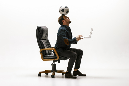 Businessman with football ball in office. Soccer freestyle. Concept of balance and agility in business. Manager perfoming tricks sitting on chair and working on laptop isolated on white studio background. Stock Photo