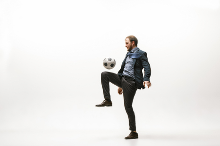 Businessman with football ball in office. Soccer freestyle. Concept of balance and agility in business. Manager perfoming tricks isolated on white studio background.