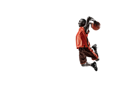 Full length portrait of a basketball player with a ball isolated on white studio background. advertising concept. Fit african american athlete jumping with ball. Motion, activity, movement concepts.