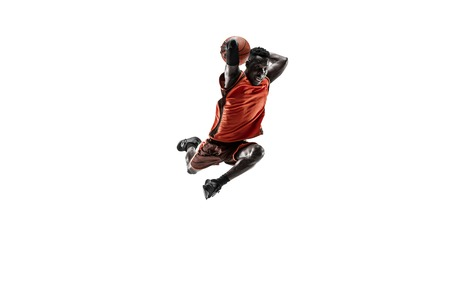 Full length portrait of a basketball player with a ball isolated on white studio background. advertising concept. Fit african anerican athlete jumping with ball. Motion, activity, movement concepts. Stock Photo
