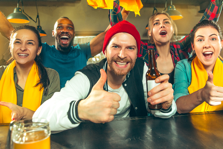 Sport, people, leisure, friendship, entertainment concept - happy male and female football fans or good young friends drinking beer, celebrating victory at bar or pub. Human positive emotions concept