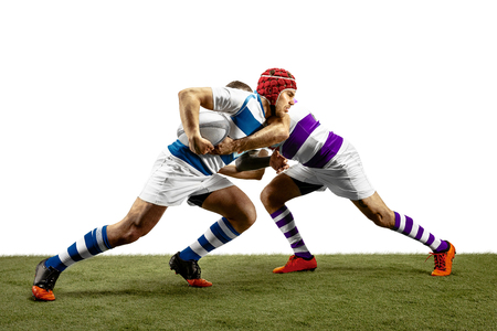 The silhouette of two caucasian rugby male players isolated on white background. Studio shot of fit men in motion or movement with ball. Jump and action concept. An incredible strain of all forces. 免版税图像