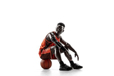 Full length portrait of a basketball player with a ball isolated on white studio background. advertising concept. Fit african anerican athlete sitting on ball.