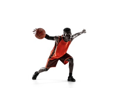 Full length portrait of a basketball player with a ball isolated on white studio background. advertising concept. Fit african anerican athlete with ball. Motion, activity, movement concepts. Stock Photo