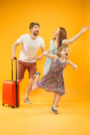 Happy surprised parent with daughter and suitcase at studio isolated on yellow background. Travel, vacation, parenthood, togetherness, tourism concept.