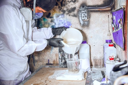 Master painter in a factory - industrial painting wood with spray gun. Stock Photo