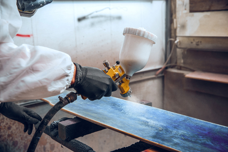 Master painter in a factory - industrial painting wood with spray gun. 写真素材