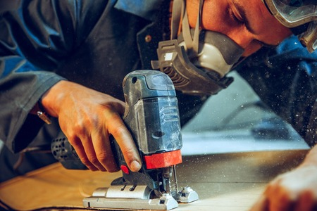 Carpenter using circular saw for cutting wooden boards. Construction details of male worker or handy man with power tools Banque d'images - 118696211