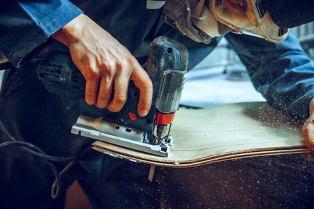 Carpenter using circular saw for cutting wooden boards. Construction details of male worker or handy man with power tools Banque d'images - 118696240