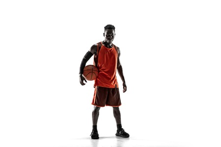 Full length portrait of a basketball player with a ball isolated on white studio background. advertising concept. Fit african anerican athlete standing with ball.