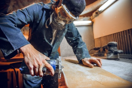 Carpenter using circular saw for cutting wooden boards. Construction details of male worker or handy man with power tools Banque d'images - 118696295