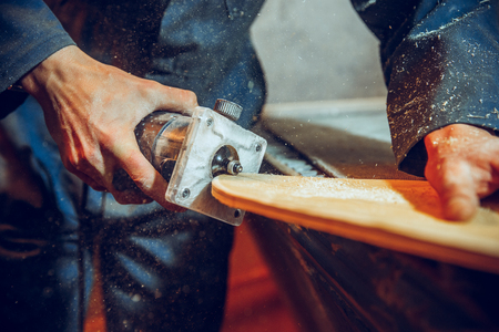 Carpenter using circular saw for cutting wooden boards. Construction details of male worker or handy man with power tools Banque d'images - 118696297