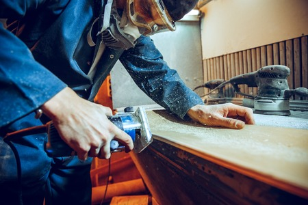 Carpenter using circular saw for cutting wooden boards. Construction details of male worker or handy man with power tools Stock fotó - 118702312