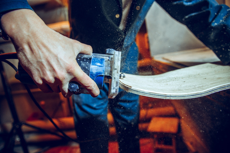 Carpenter using circular saw for cutting wooden boards. Construction details of male worker or handy man with power tools Banque d'images - 118702315
