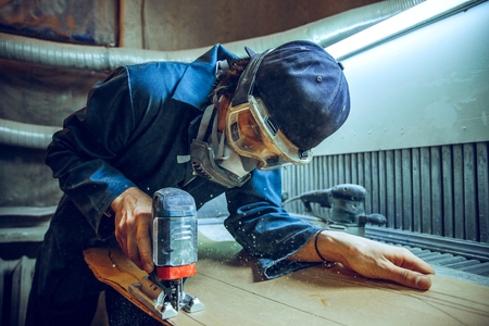 Carpenter using circular saw for cutting wooden boards. Construction details of male worker or handy man with power tools Banque d'images - 118700754