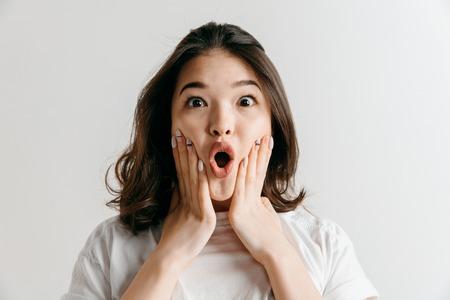Wauw. Mooie vrouwelijke halve lengte front portret geïsoleerd op grijze studio achtergrondgeluid. Jonge emotionele verraste aziatische vrouw die zich met open mond bevindt. Menselijke emoties, gezichtsuitdrukking concept.