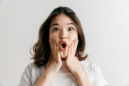 Wow. Beautiful female half-length front portrait isolated on gray studio backgroud. Young emotional surprised asian woman standing with open mouth. Human emotions, facial expression concept. Stock Photo
