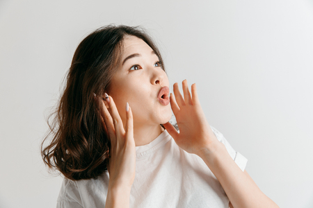 Do not miss. Young casual woman shouting. Shout. Crying emotional woman screaming ongray studio background. Female half-length portrait. Human emotions, facial expression concept.